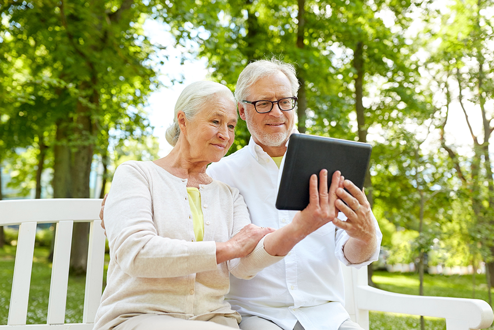 Couple holding a tablet to view their inspection report created by one our home inspectors