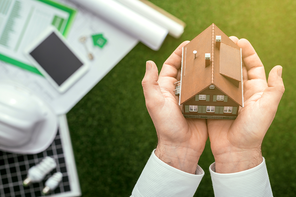 Insurance agent holding a model house, drafts, solar panel and safety helmet on the background, after a home inspection